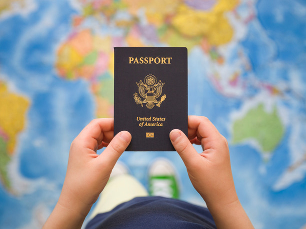 Passport being held over a map of the World