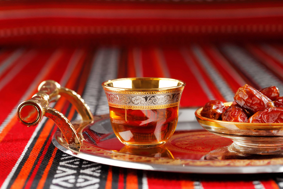 Arabic tea and dates on an ornate tray